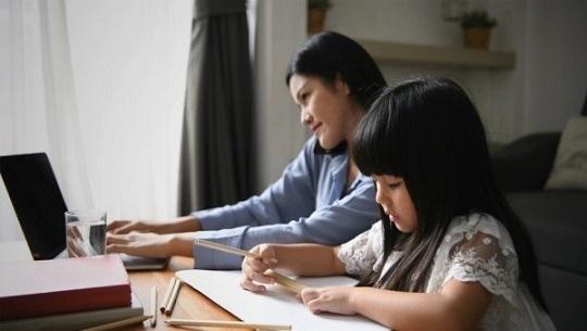 一成人和一小孩在各自工作和學習
