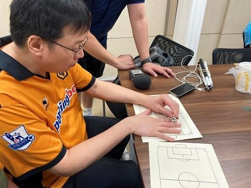 會員在觸摸用感熱紙製作「凸起」的足球場平面圖